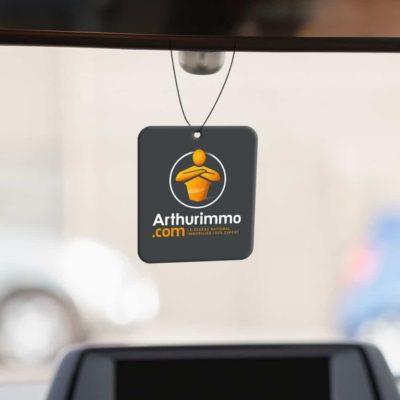 Mise en situation numérique du recto avec fond pour le modèle 2 de désodorisant voiture pour la franchise Arthurimmo. Choisissez le modèle, sa version, nous personnaliserons votre support de communication.