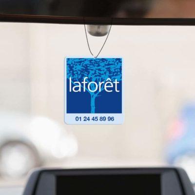 Mise en situation numérique du recto avec fond pour le modèle 1 de désodorisant voiture pour la franchise Laforêt. Choisissez le modèle, sa version, nous personnaliserons votre support de communication.